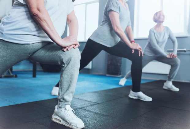 Forget about your joint pain. Scale up shot of a group of senior ladies standing in a row and doing lunging exercises while all three training in a gym.